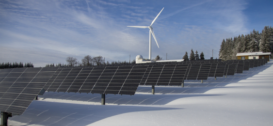 Solar panels and wind turbines on top of snow